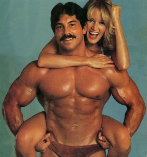 Ray Mentzer holding a woman in a photo shoot looking ripped