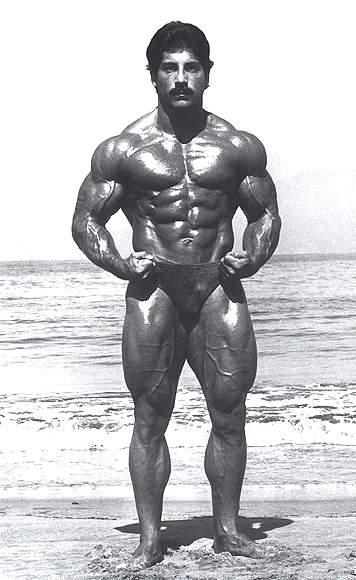 Ray Mentzer posing shirtless on the beach in a black and white photo, looking muscular and ripped