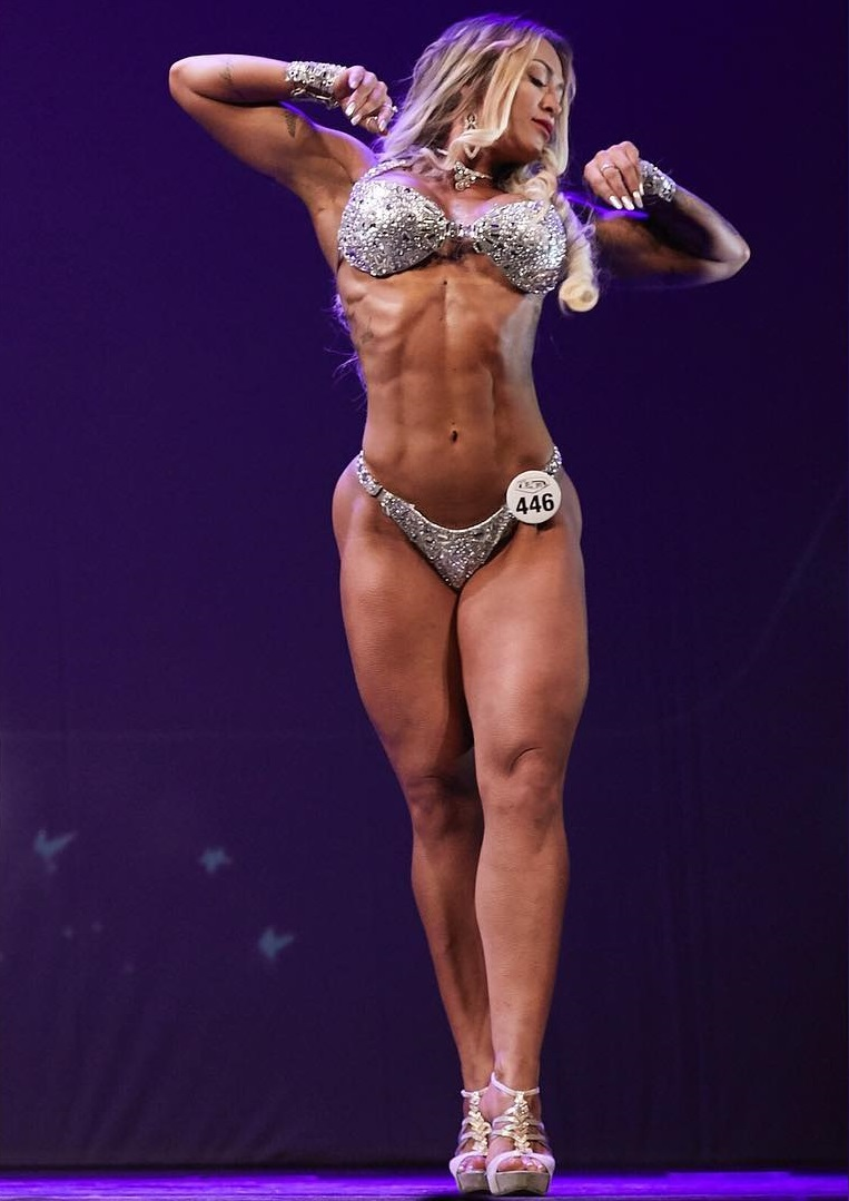Rochelle Michielin posing on the WBFF stage in her shiny bikini outfit