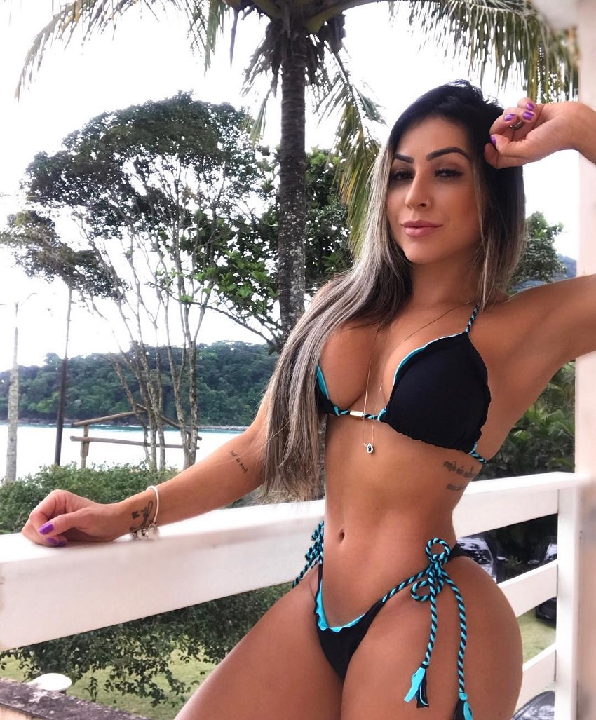 Tatiane Almeida looking fit and lean in a photo standing on a balcony