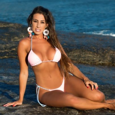 Thais Eid sitting on a rock on the beach in her white bikini, looking fit and lean