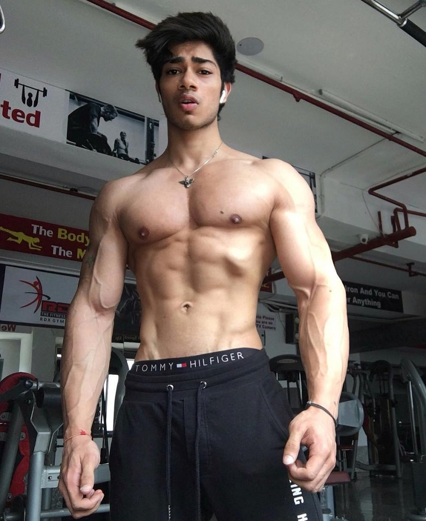 Vasu Mittal posing in the gym looking strong and ripped