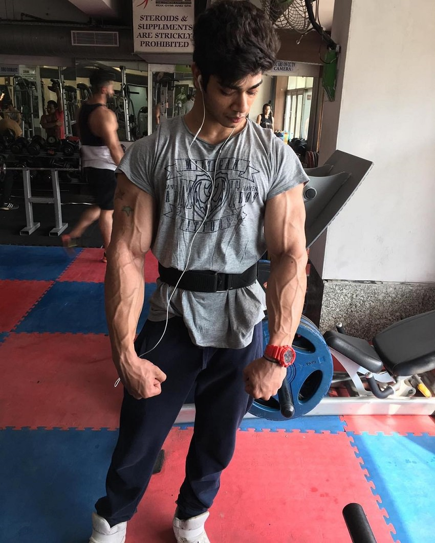 Vasu Mittal posing in a gym looking vascular and ripped