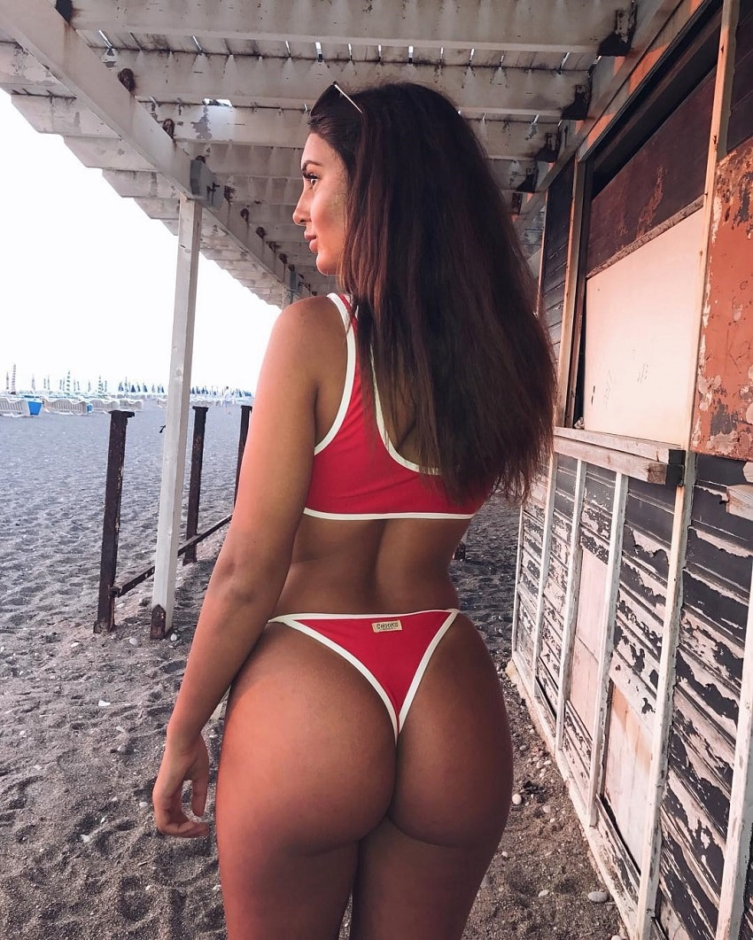 Amanda Fransson standing on the beach, showcasing her curvy glutes in a red bikini