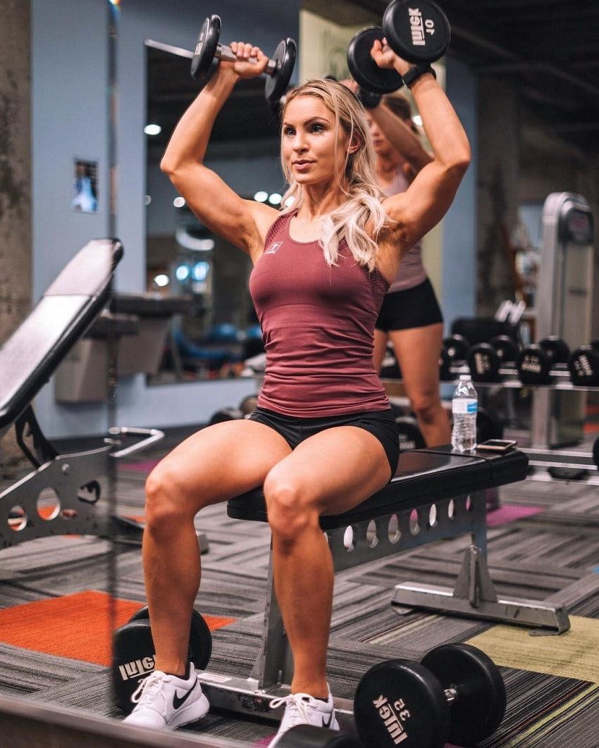 Ashley Nordman doing seated dumbbell shoulder press in the gym looking fit