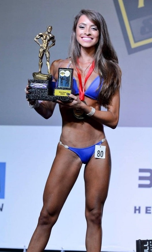 Bruna Montenegro posing on the fitness stage with a trophy