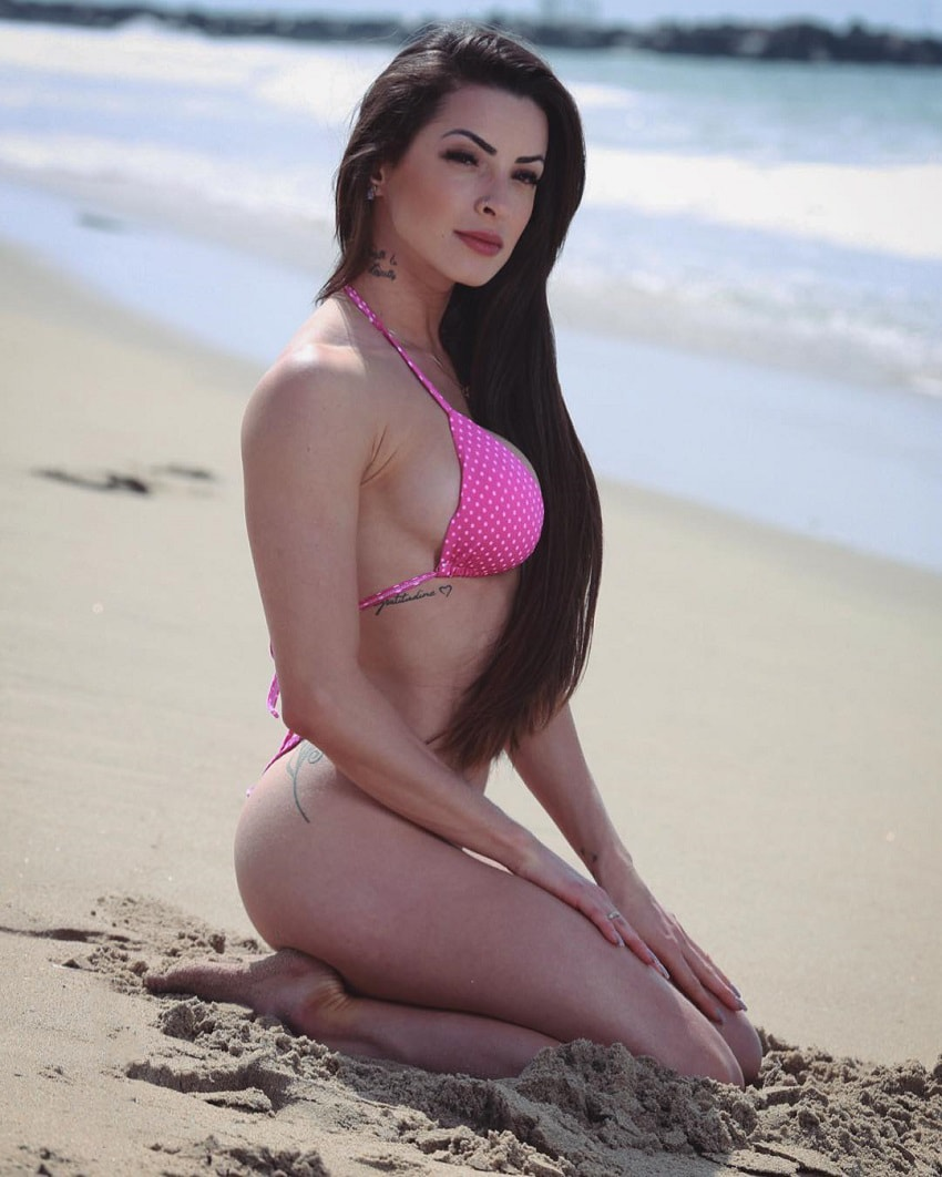 Bruna Montenegro posing on the beach in a pink bikini looking fit and lean