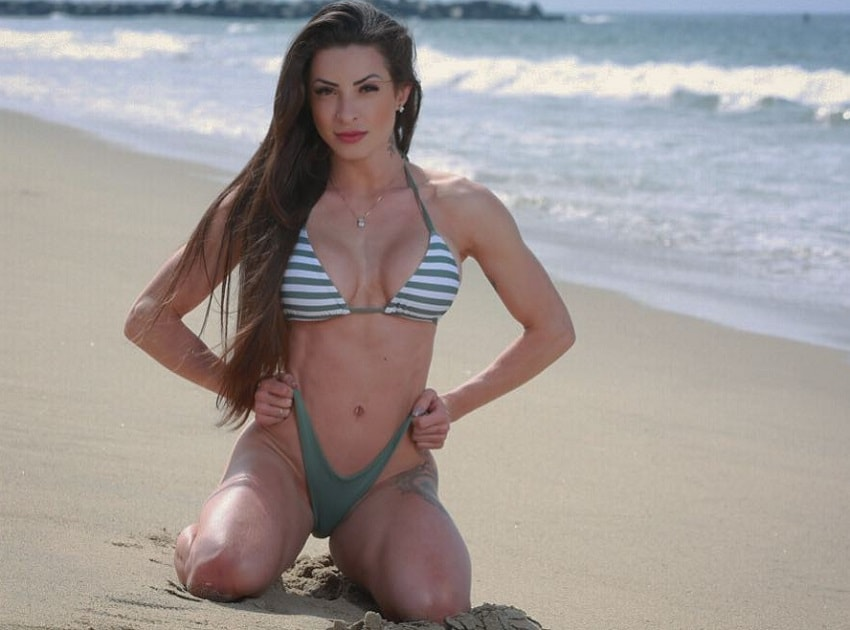 Bruna Montenegro kneeling on the beach in her bikini looking aesthetic