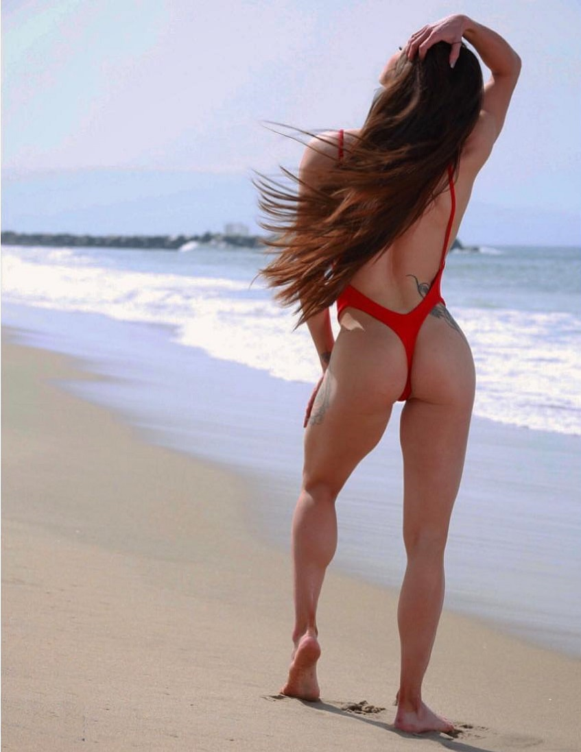 Bruna Montenegro showing off her glutes in a red swimsuit on the beach