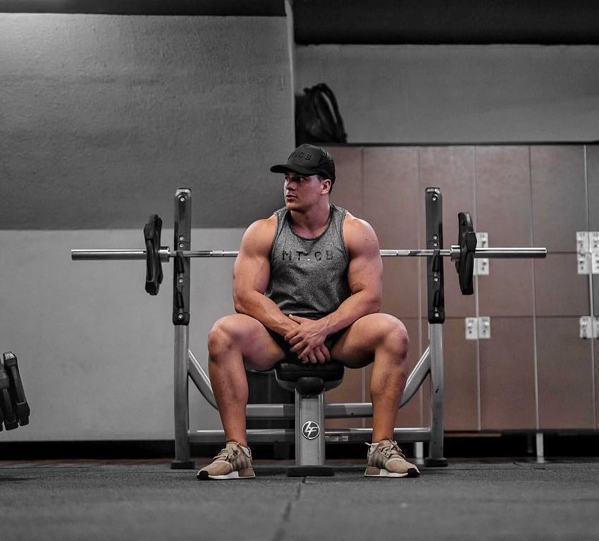 Caio Bottura sitting on the bench in the gym looking swole and muscular