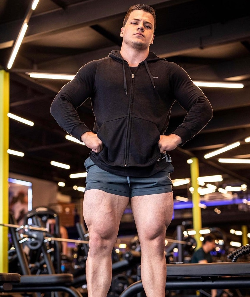 Caio Bottura posing in the gym showing off his huge legs