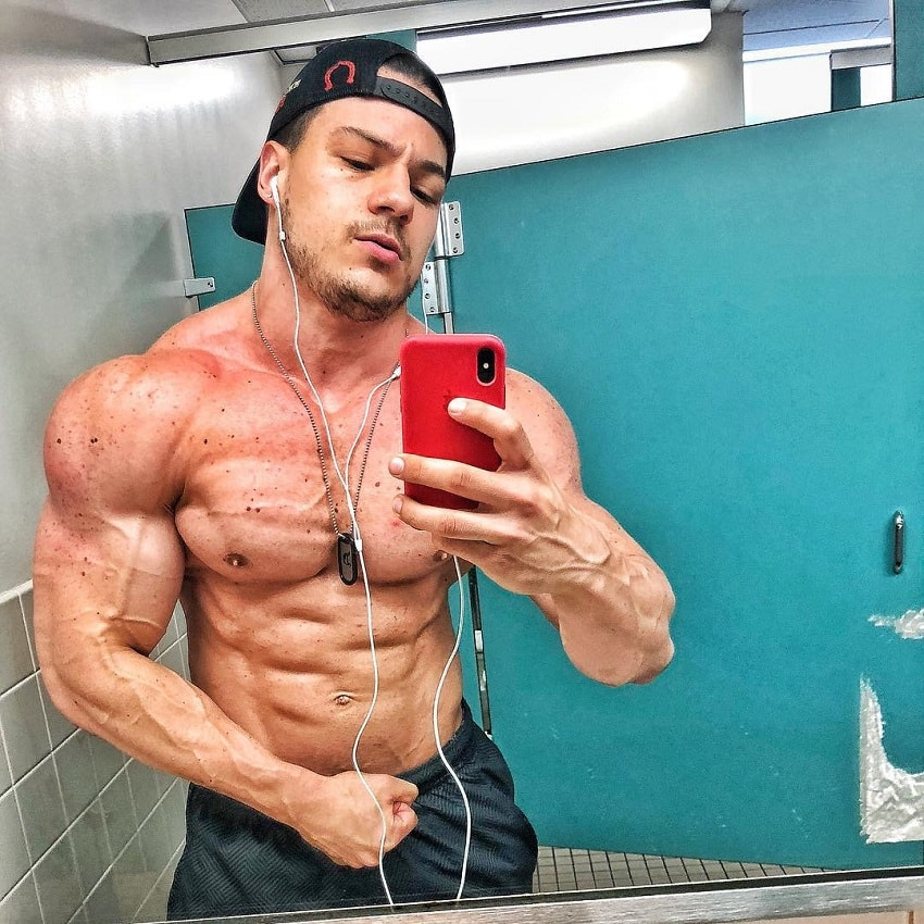 Caio Bottura taking a shirtless selfie looking ripped and vascular
