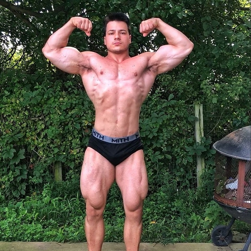 Caio Bottura performing a shirtless front double biceps pose in his backyard, looking ripped and muscular
