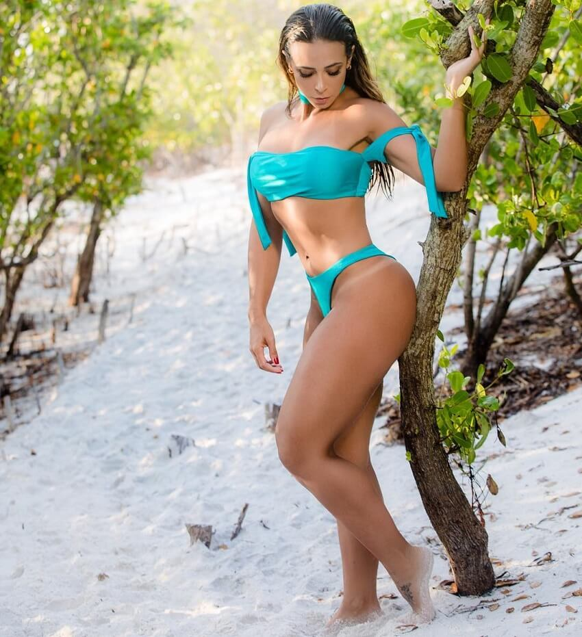 Carol Porcelli posing by a tree looking fit