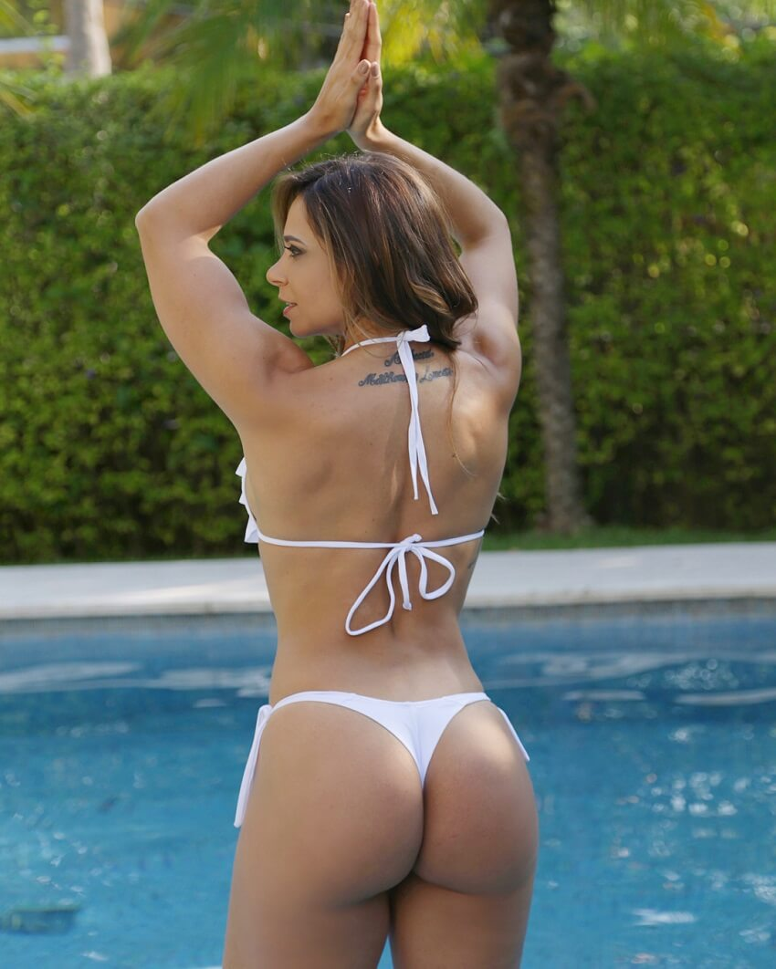 Carol Porcelli standing in the pool, her glutes looking curvy and toned