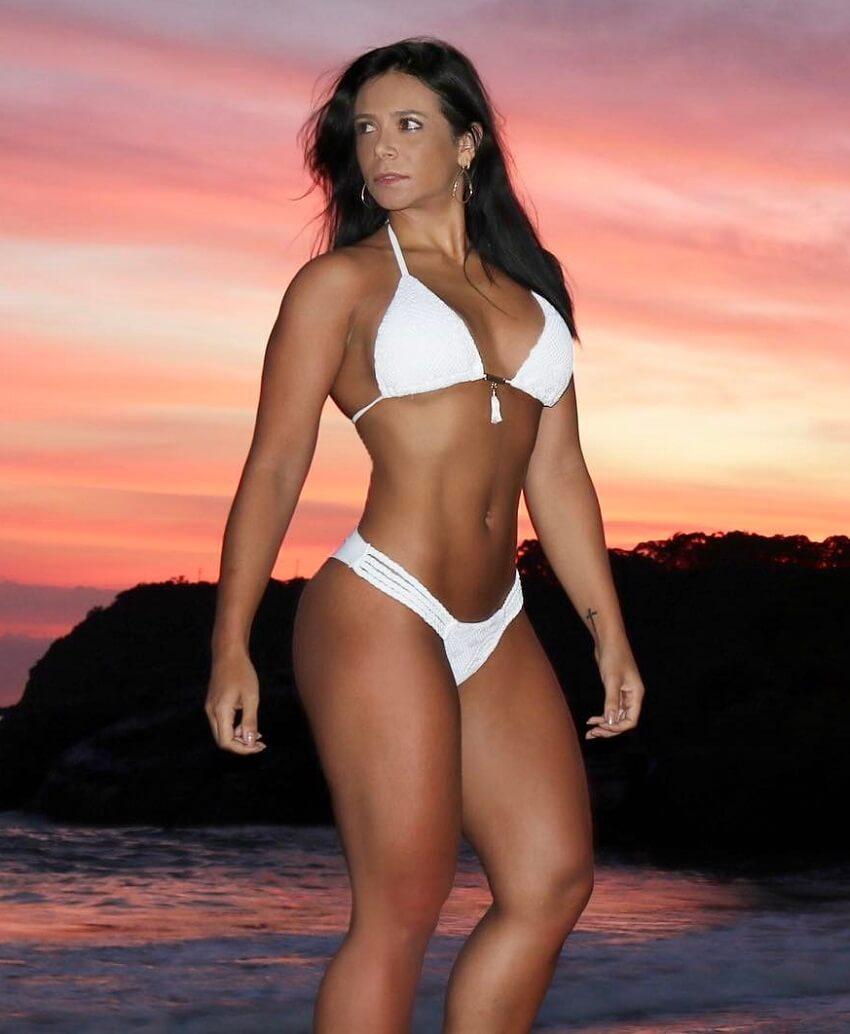 Carol Porcelli posing on the beach in a white bikini