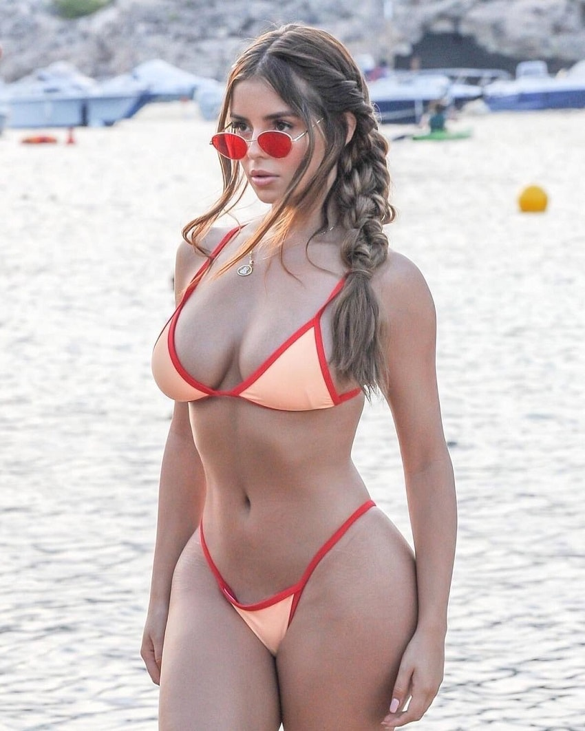 Demi Rose Mawby standing on the beach wearing red sunglasses and a bikini, looking curvy and fit