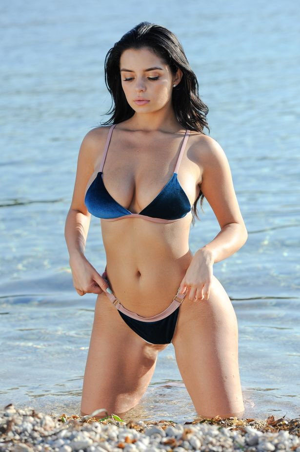 Demi Rose Mawby kneeling on the beach in her bikini looking curvy and lean