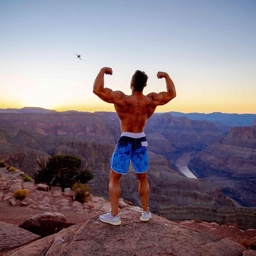 Diogo Montenegro doing a shirtless back double biceps outdoors on a barren hill overlooking a huge canyon