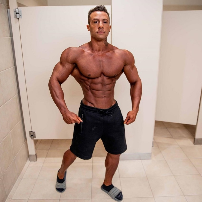 Diogo Montenegro posing shirtless in a gym locker room, looking tanned up and aesthetic