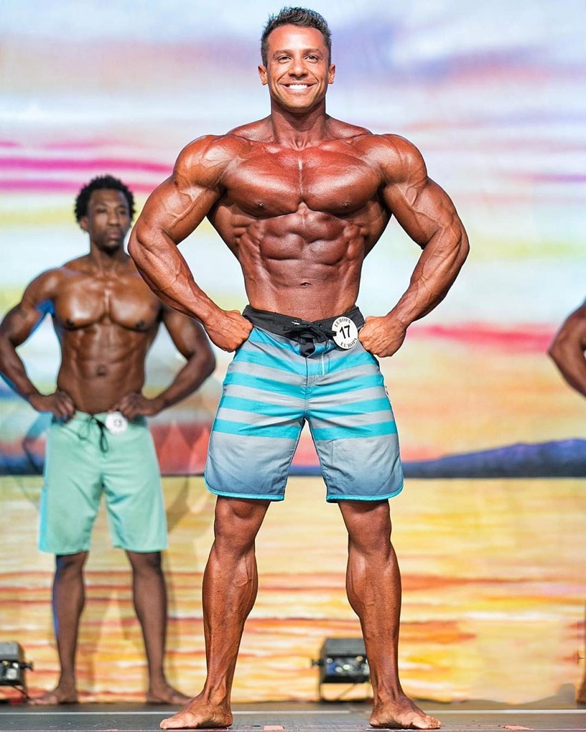 Diogo Montenegro posing on the Men's Physique stage, showcasing his ripped chest, arms, and midsection