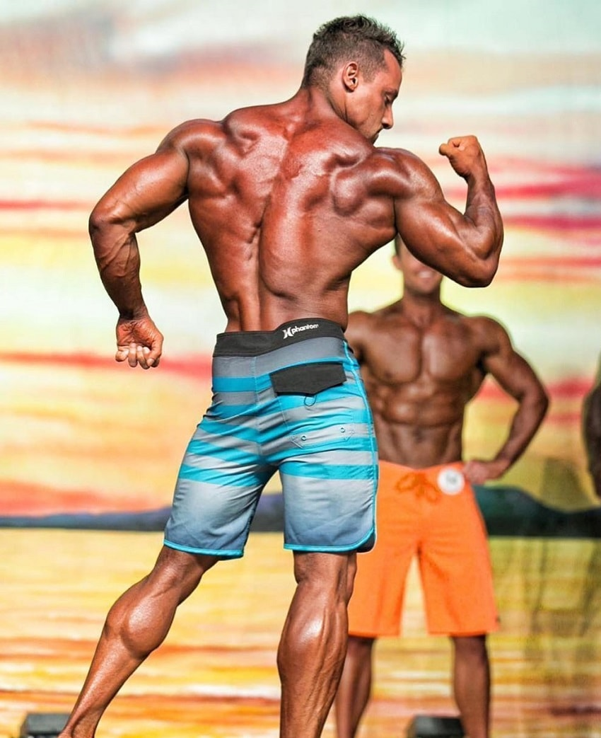 Diogo Montenegro posing on the men's physique stage, his back looking muscular and ripped