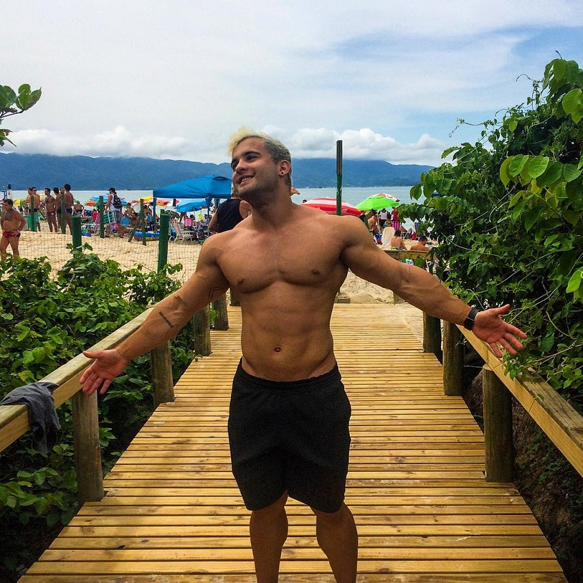 Ernane Guimaraes shirtless, walking down the beach resort, looking happy and fit