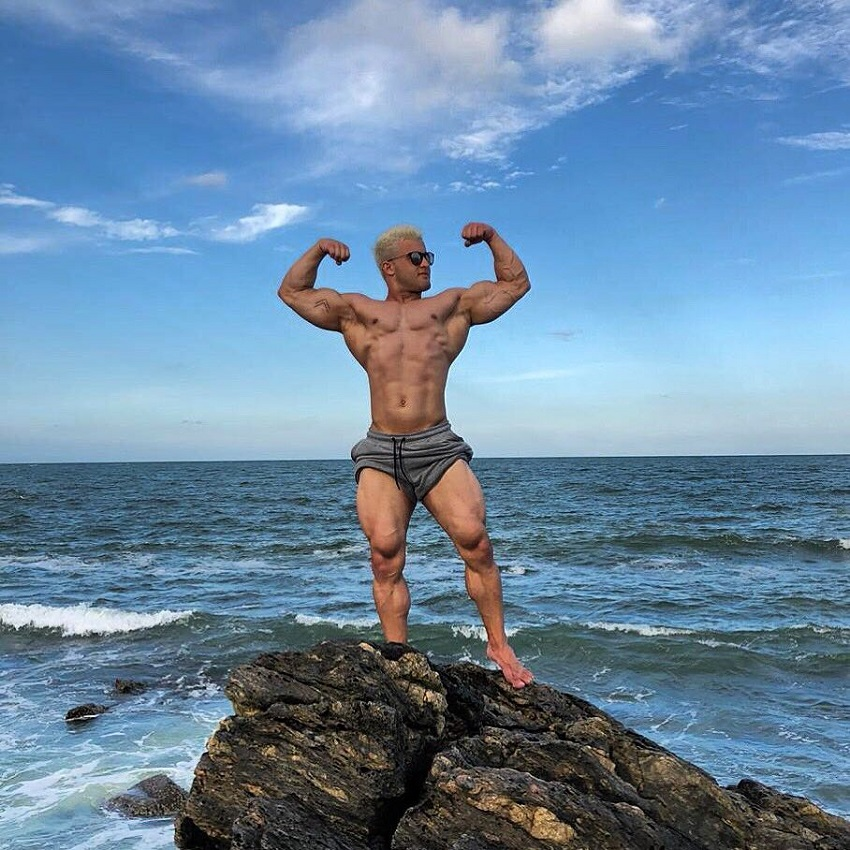 Ernane Guimaraes flexing front double biceps on the rock by the sea