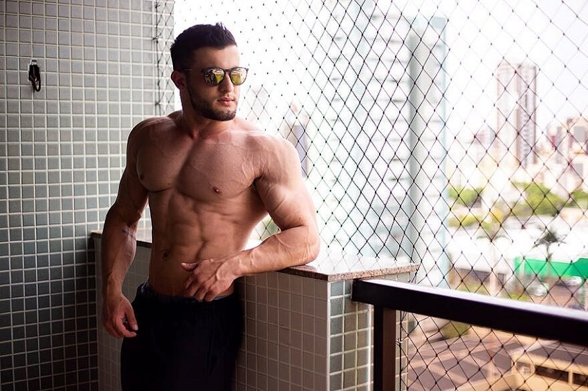 Ernane Guimaraes posing shirtless on the balcony with sunglasses on, looking fit and ripped
