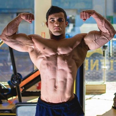 Ernane Guimaraes flexing shirtless front double biceps