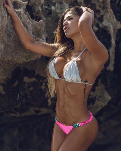 Estefania Pereira posing by the rock flexing her abs