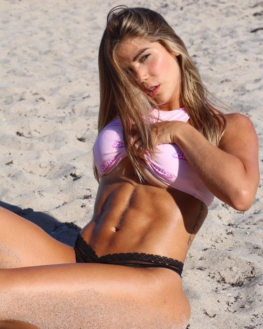 Estefania Pereira lying on the beach flexing her abs