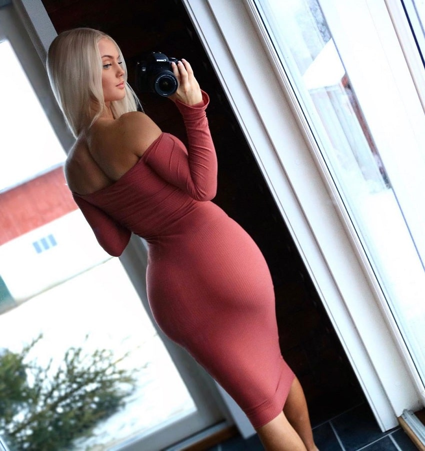Filippa Fransson taking a selfie of her curvy glutes in an elegant red dress