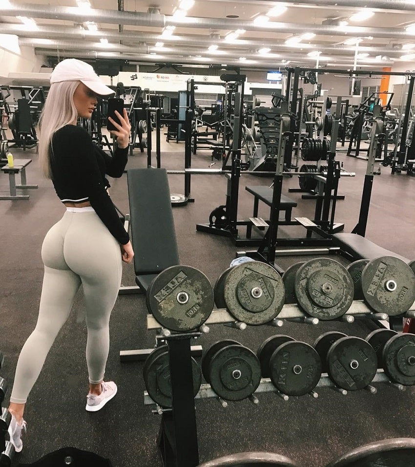 Filippa Fransson photographing herself in the gym near the dumbbell rack