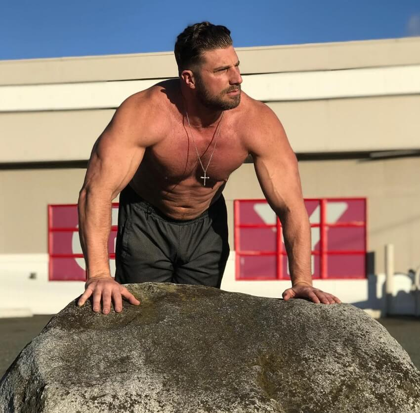Gabe Moen leaning against the rock, looking strong and big