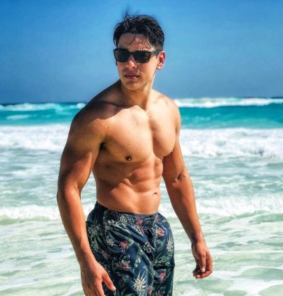 Gabriel Arones standing shirtless on the beach with black sunglasses, looking fit and strong