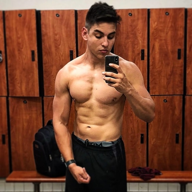 Gabriel Arones taking a selfie of his shirtless muscular body in a gym locker room