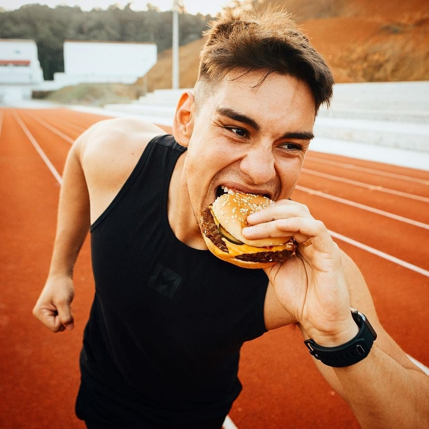 Gabriel Arones eating a burger outdoors on a track field