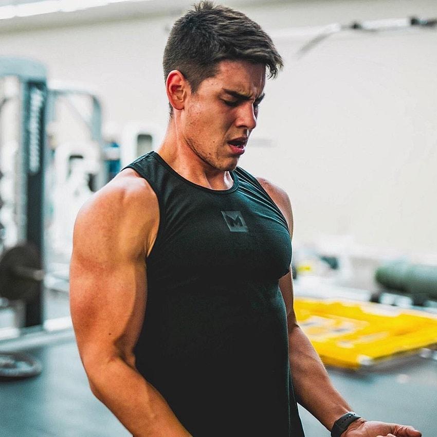 Gabriel Arones lifting heavy biceps curls in the gym