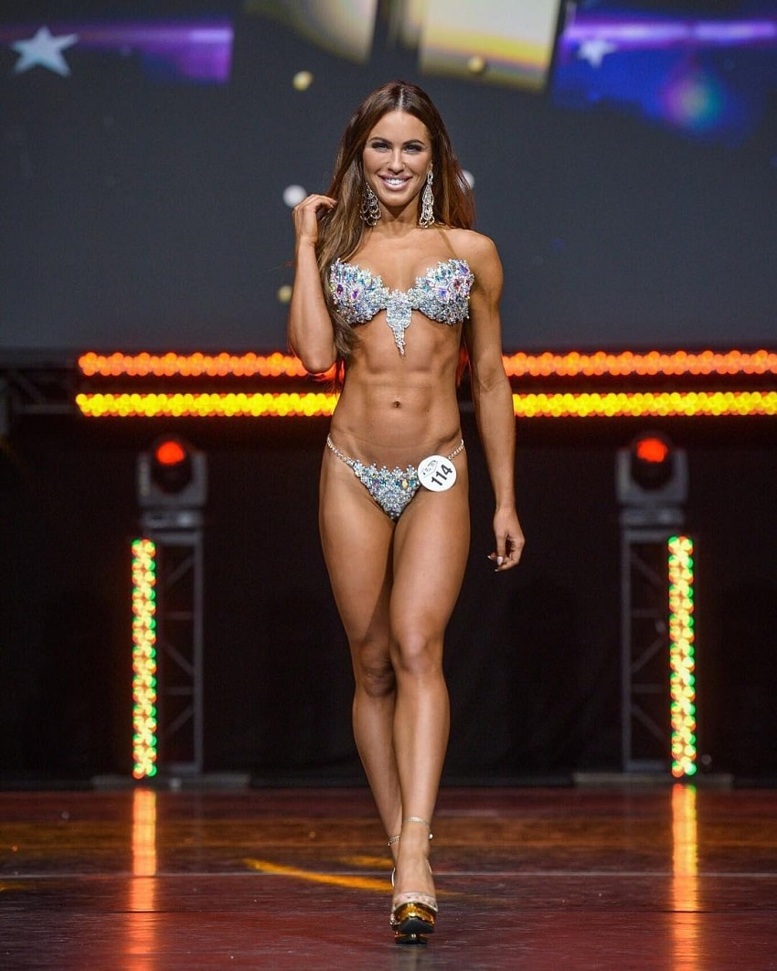 Jade Katy walking down the WBFF Fitness Model stage looking spectacular