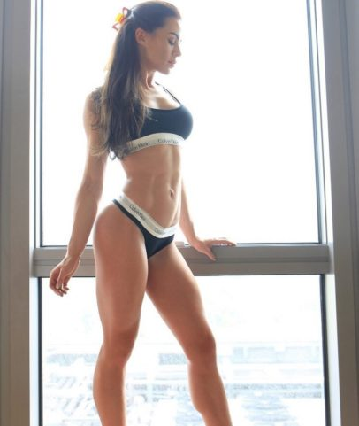 Jade Katy posing by a window in her sports bra and underwear looking fit and lean