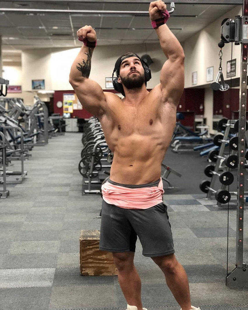 Jake Burton flexing his muscles shirtless in the gym looking up at the ceiling