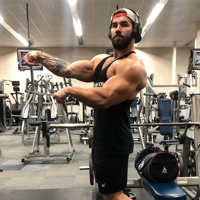 Jake Burton flexing his arms old-school Arnold style while standing in the gym