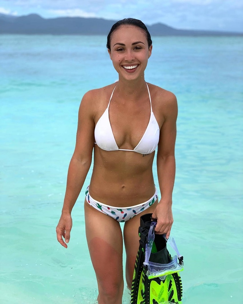 Katie Jean standing half-way in the sea in her white bikini and smiling for the photo