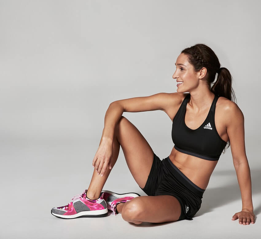 Kayla Itsines sitting on the floor posing for a fitness photo shoot