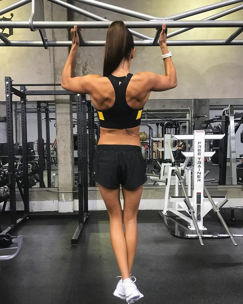 Kayla Itsines doing pull-ups in the gym