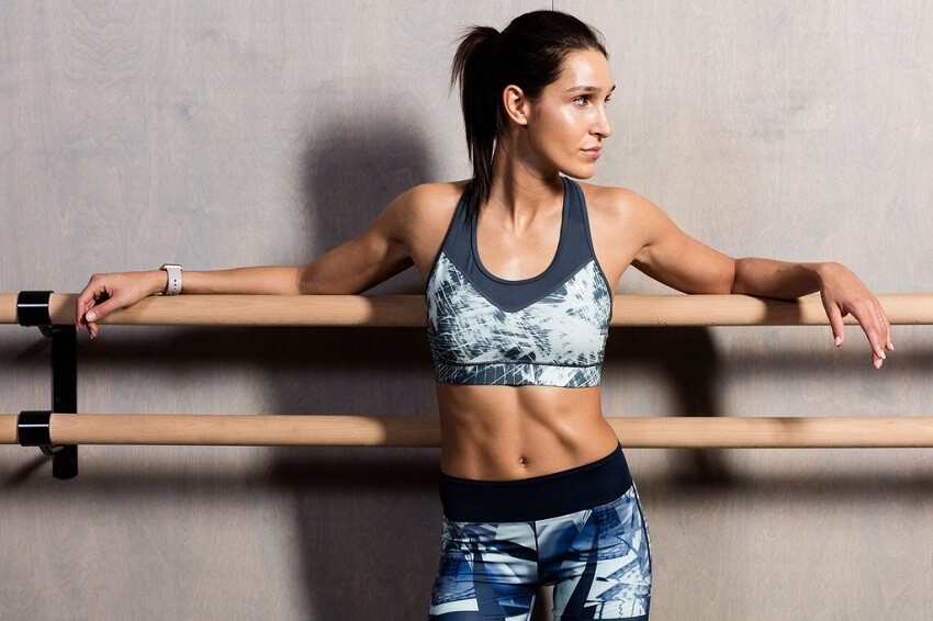 Kayla Itsines posing in her sports clothes, looking fit and lean