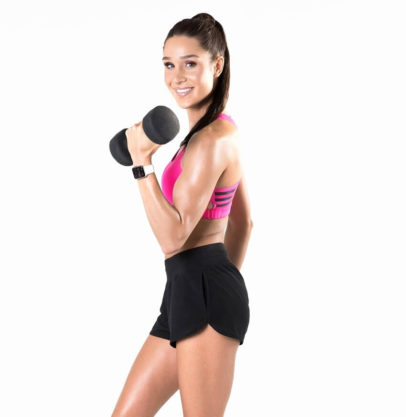 Kayla Itsines posing with a dumbbell in a fitness photo shoot