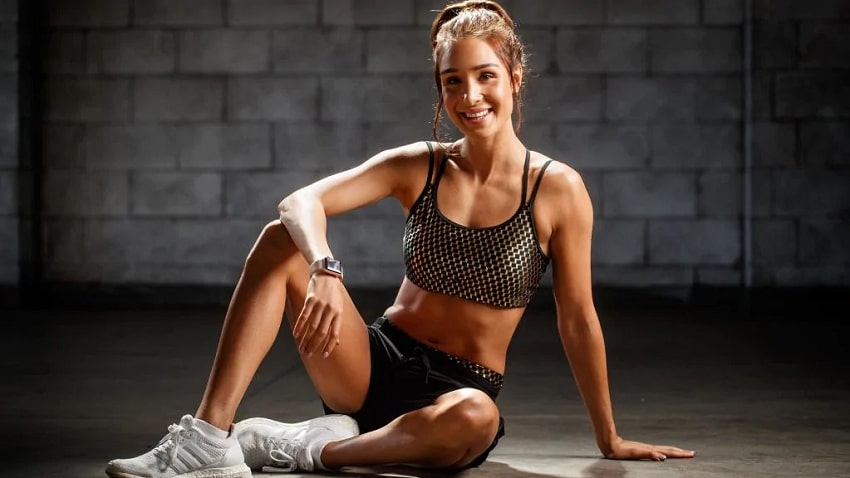 Kayla Itsines smiling in a fitness photo shoot looking fit and lean