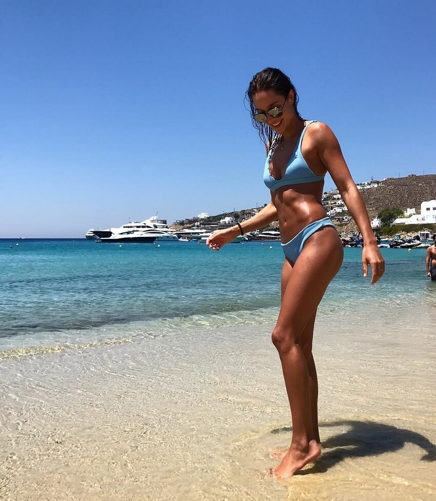 Kayla Itsines posing on the beach looking lean